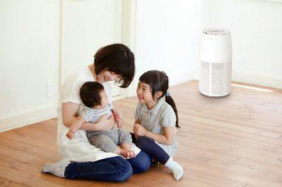 リビングルームに赤ちゃんを抱く母親と娘、その傍らに高性能の空気清浄機